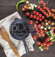 cast iron round frying pan and ripe red cherry tomatoes