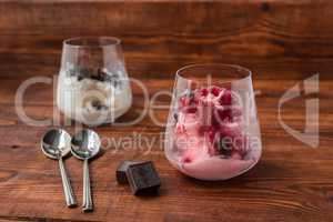 Sweet desert with ice cream, chocolate and berries on wooden table