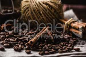 Coffee beans with autumn spices on the tablecloth.