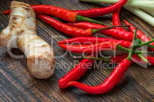 Galangal root, hot mini chili peppers with lemongrass on wooden table