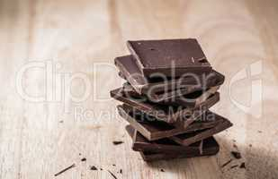 Chocolate Bars Stack on Wooden Table.