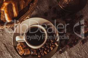 cup of coffee on textile with beans and sugar