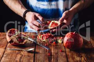 Opened Pomegranate Fruit in Hands
