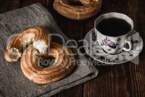 Round eclairs with cup of coffee