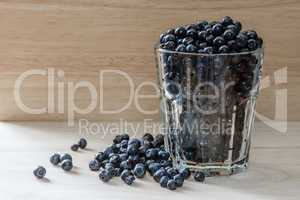 Blueberries in glass with scattered berries. Good addition for breakfast