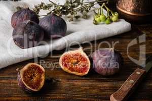 Ripe figs on cloth with sliced one and some objects