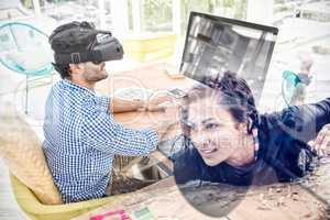Composite image of graphic designer in virtual reality simulator while using computer