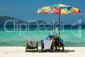 Beach umbrella chairs and boat in Coral island, Thailand