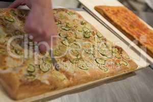 Pizza maker cutting italian pizza