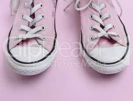 pair of old worn pink sneakers with white laces