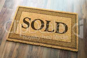 Sold Welcome Mat On A Wood Floor Background