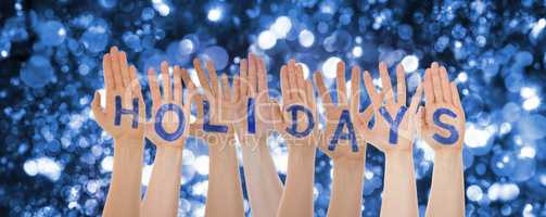 Hands Building Word Holidays, Glittering And Sparkling Bokeh Background