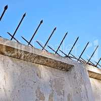 Old concrete fence with two-sided acute iron pins