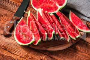 Watermelon half and slices lying on wooden table