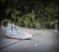 pair of old worn blue textile sneakers on gray asphalt