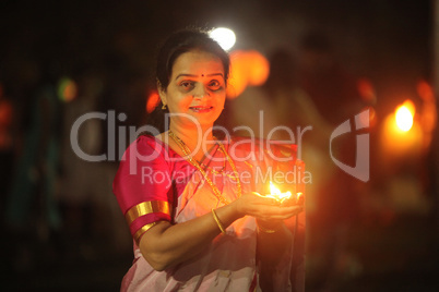 Pune, India - November 2018: A woman lights up a lamp during a p