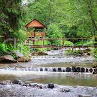 Mountain river, lush vegetation and recreation area with a bridg