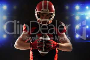 American football player in helmet holding rugby ball