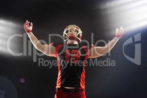 American football player standing against black background