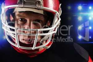 American football player in helmet standing against black background
