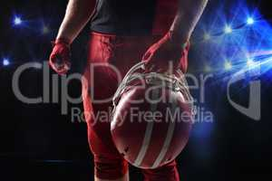 American football player standing with helmet against black background