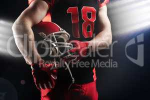American football player holding rugby helmet