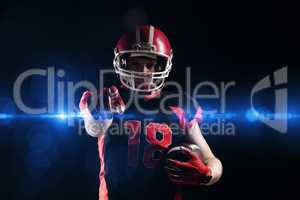 American football player in helmet holding rugby ball and pointing