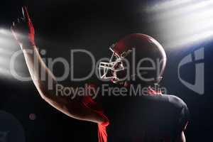 American football player in helmet pointing upwards