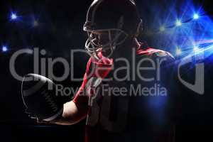 American football player with helmat looking at rugby ball