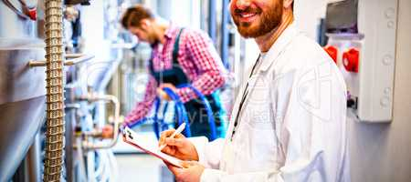 Maintenance workers examining brewery machine