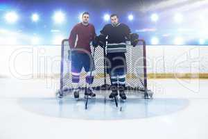 Composite image of ice hockey players standing by goal post