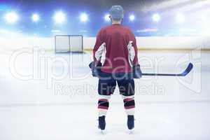 Composite image of rear view of hockey player at ice rink