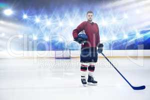 Composite image of portrait of ice hockey player holding helmet and stick