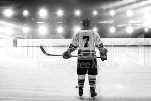 Composite image of hockey player with hockey stick standing on rink