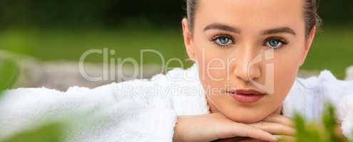 Beautiful Young Woman Relaxing in Robe at Health Spa