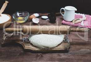piece of white wheat flour dough on a brown board