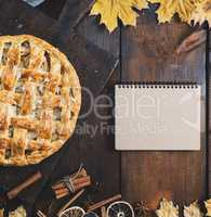 baked apple pie on a board and a notebook with a blank page for
