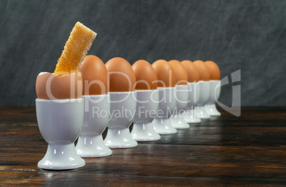 Row of Boiled Eggs in Egg Cups on a Table