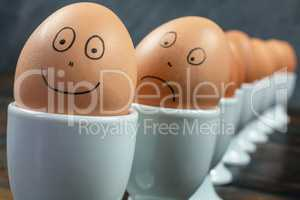 Happy and Sad Emotion Concept Eggs in Egg Cups on a Table
