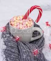 ceramic cup with hot chocolate with marshmallows on white snow w