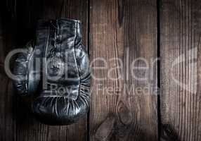 one very old leather black boxing glove with laces