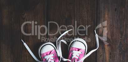 small pink textile sneakers on a brown wooden background