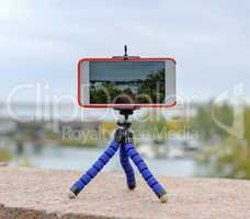 smartphone stands on tripod and shoots landscape