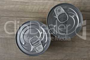 Tin cans for food on wooden background.
