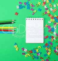 notebook with empty white sheets and multicolored wooden pencils