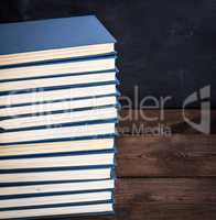 stack of books in a blue cover on a brown wooden table
