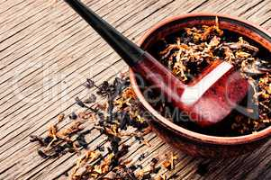 Pipe and tobacco on rustic background