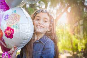 Cute Young Mixed Race Girl Holding Mylar Balloon Outdoors