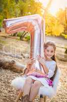 Cute Young Girl Playing With Number Seven Mylar Balloon Outdoors