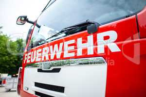 German fire engine stands on a deployment site. The german word Feuerwehr means fire department.